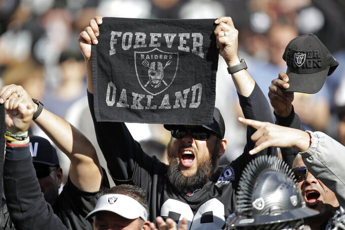 An Oakland Raiders fans holds up a towel and cheers during the first half of an NFL football game against the Jacksonville Jaguars in Oakland, Calif., Sunday, Dec. 15, 2019. (AP Photo/Ben Margot)
