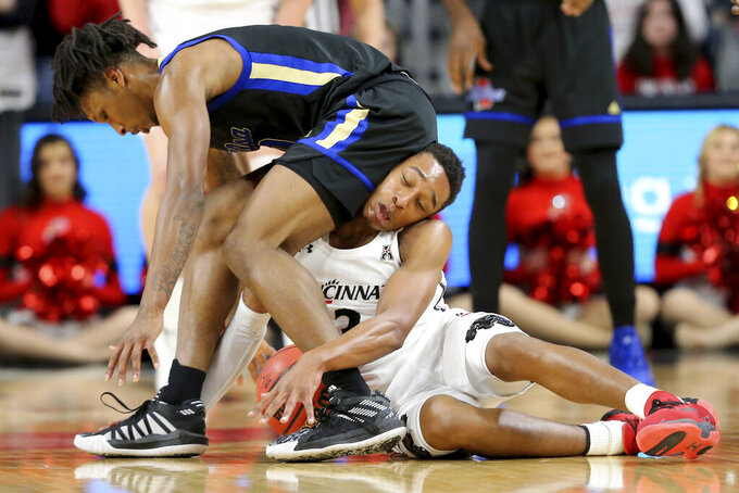 Tulsa center Emmanuel Ugboh, left, and Cincinnati guard Mika Adams-Woods (3) compete for a loose ball during the first half of an NCAA college basketball game Wednesday, Jan. 8, 2020, in Cincinnati. (Kareem Elagazzar/The Cincinnati Enquirer via AP)