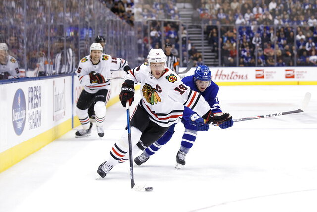 Chicago Blackhawks centre Jonathan Toews (19) skates with the puck as Toronto Maple Leafs centre Adam Brooks trails during first period NHL hockey action in Toronto, Saturday, Jan. 18, 2020. (Cole Burston/The Canadian Press via AP)