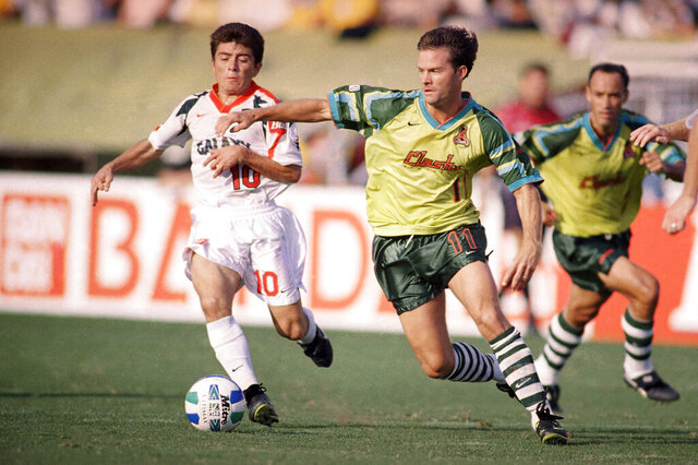 FILE - In this Sept. 15, 1996, file photo, Los Angeles Galaxy's Mauricio Cienfuegos (10) pursues San Jose Clash's Eric Wynalda during the first half of an MLS soccer game at the Rose Bowl in Pasadena, Calif. Before the first-ever Major League Soccer match on April 6, 1996, a group of Clash players went to a trendy San Jose restaurant for some pre-game bonding, and four of them threw up after the meal. But it had nothing to do with the food, recalled Wynalda.