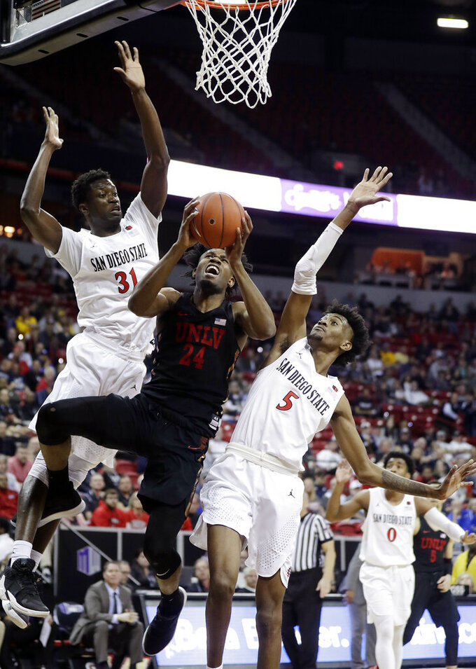 San Diego State's Nathan Mensah (31) and Jalen McDaniels (5) defend as UNLV'sJoel Ntambwe shoots during the second half of an NCAA college basketball game in the Mountain West Conference men's tournament Thursday, March 14, 2019, in Las Vegas. (AP Photo/Isaac Brekken)