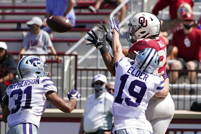 Oklahoma running back Jeremiah Hall (27) reaches for a touchdown pass between Kansas State defensive back Jahron McPherson (31) and defensive back Ross Elder (19) in the second half of an NCAA college football game Saturday, Sept. 26, 2020, in Norman, Okla. (AP Photo/Sue Ogrocki).