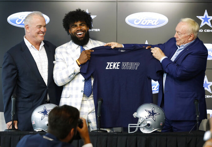 From left to right, Dallas Cowboys director of player personnel Stephen Jones watches as running back Ezekiel Elliott is presented with a shirt by team owner Jerry Jones, right, during a news conference regarding Elliott's new contract at the NFL football team's practice facility in Frisco, Texas, Thursday, Sept. 5, 2019. Elliott's agreement on a new contract ended a holdout that covered all of training camp and the preseason and came four days before the season opener at home against the New York Giants. (AP Photo/Tony Gutierrez)