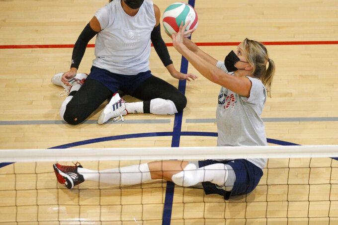 Lora Webster with the U.S. women's sitting volleyball team, sets the ball during  practice in Edmond, Okla., on July 24, 2021. She's five months pregnant and expecting her fourth child. This is the second Paralympics in which she's been pregnant, and the third time during a competition. She and her American teammates face Brazil on Friday, Sept. 3, 2021, in the semifinals as Webster tries for her fifth Paralympic medal. (Bryan Terry/The Oklahoman via AP)