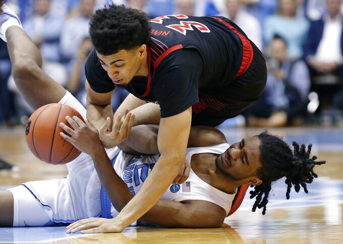North Carolina's Coby White, bottoom, and Louisville's Jordan Nwora go to the floor chasing the ball during the second half of an NCAA college basketball game in Chapel Hill, N.C., Saturday, Jan. 12, 2019. Louisville won 83-62. (AP Photo/Gerry Broome)