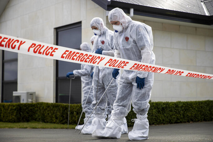 Police search the driveway of a house where three children were found dead in the South Island town of Timaru, New Zealand, Friday, Sept. 17, 2021. Three young children who had just moved to New Zealand from South Africa have died in what police are investigating as homicide. (George Heard/New Zealand Herald via AP)