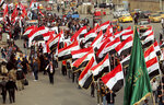 People hold national flags and chanting religious slogans march in Tahrir Square in Baghdad, Iraq, Friday, Dec. 6, 2019. (AP Photo/Hadi Mizban)