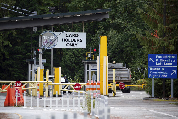A U.S. Customs and Border Protection officer working at the Point Roberts-Boundary Bay border crossing, in Point Roberts, Wash., is seen from Delta, British Columbia, on Wednesday, Oct. 13, 2021. Point Roberts sits on a peninsula and is only accessible by land by travelling through Canada. Beleaguered business owners and families separated by COVID-19 restrictions rejoiced Wednesday after the U.S. said it will reopen its land borders to nonessential travel next month, ending a 19-month freeze. (Darryl Dyck/The Canadian Press via AP)