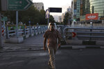 A man wearing protective face mask and shield to help prevent the spread of the coronavirus crosses a street in central Tehran, Iran, Sunday, Aug. 8, 2021. Iranians are suffering through yet another surge in the coronavirus pandemic — their country's worst yet — and anger is growing at images of vaccinated Westerners without face masks on the internet or on TV while they remain unable to get the shots. (AP Photo/Vahid Salemi)