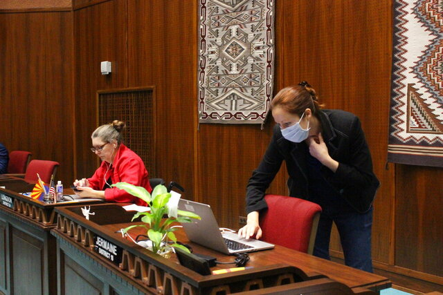 State Rep. Jennifer Jermaine, wearing a mask, looks at documents on her computer as fellow Democratic Rep. Jennifer Longdon, left, looks at her phone before the start of an unusual floor session at the Arizona House in Phoenix, on Thursday, March 19, 2020. The Legislature could work long into the night to enact a basic state budget and fixes for schools and workers before adjourning to allow the coronavirus crisis to ebb. (AP Photo/Bob Christie)