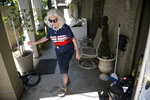 Home owner Billye Ber walks past an apartment on the ground level that was flooded after severe weather Wednesday caused street flooding in the Broadmoor neighborhood in New Orleans, Thursday, July 11, 2019.  (Max Becherer/The Advocate via AP)