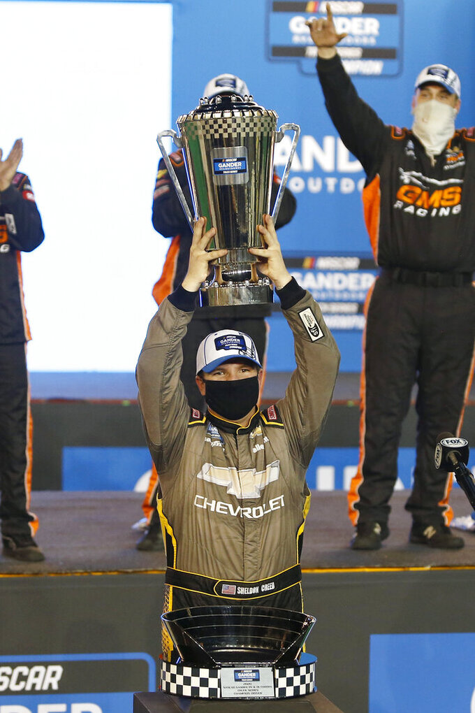 Sheldon Creed holds up the season champion's trophy in Victory Lane after winning the NASCAR Truck Series auto race at Phoenix Raceway, Friday, Nov. 6, 2020, in Avondale, Ariz. (AP Photo/Ralph Freso)