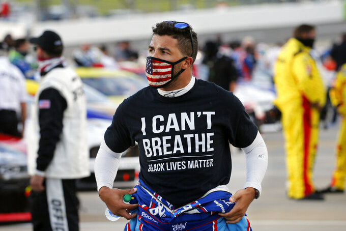 "FILE - Driver Bubba Wallace wears a Black Lives Matter shirt as he prepares for a NASCAR Cup Series auto race Wednesday, June 10, 2020, in Martinsville, Va. NASCAR drivers don't plan to boycott Saturday night's, Aug. 29 race at Daytona International Speedway to raise awareness of social and racial injustices. Bubba Wallace, the only fulltime Black driver in the elite Cup Series, said that decision should not be interpreted as ""turning away from the dark and evil acts that have taken over our nation."" (AP Photo/Steve Helber, File)"