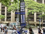"""Supporters of three Honolulu police officers charged with murder and attempted murder in a shooting that killed a 16-year-old Micronesian boy wave flags that read """"Back Dah Blue"""" outside a courthouse on Tuesday, July 20, 2021 in Honolulu. A judge is scheduled to consider whether there's probable cause to support the charges. (AP Photo/Jennifer Sinco Kelleher)"""