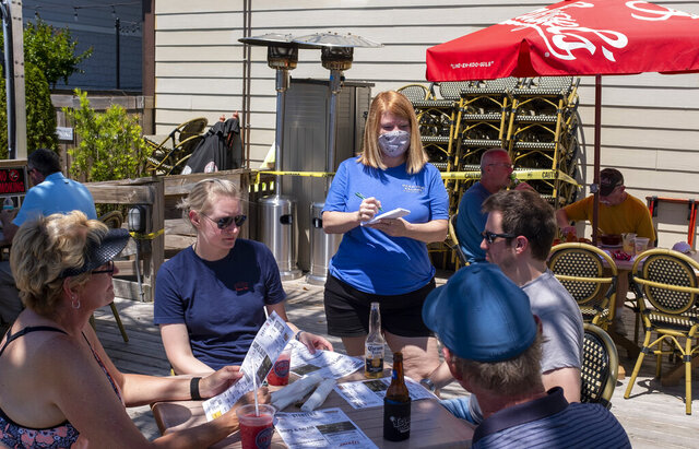 Jennifer Inman, wearing a mask, serves a table of diners at Dead Dog Saloon in Murrells Inlet, S.C. Rules for outdoor dining in South Carolina amid the coronavirus were relaxed on Monday. May 4, 2020. (Jason Lee/The Sun News via AP)