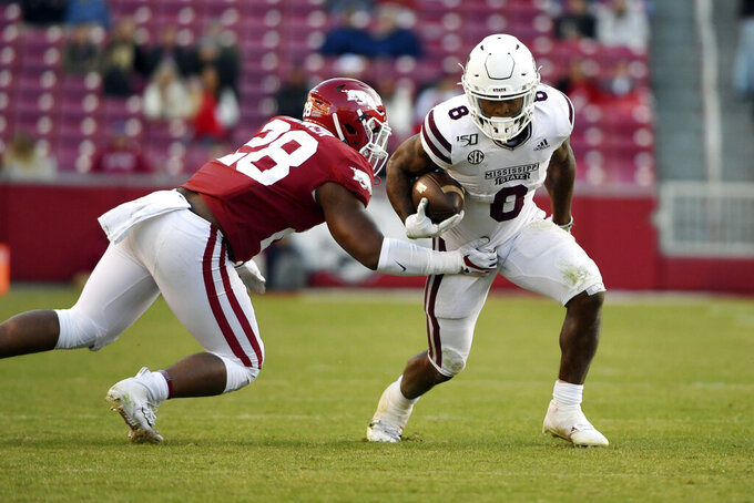 Mississippi State running back Kylin Hill (8) shakes Arkansas defender Andrew Parker (28) as he runs for a gain during the second half of an NCAA college football game, Saturday, Nov. 2, 2019, in Fayetteville, Ark. (AP Photo/Michael Woods)
