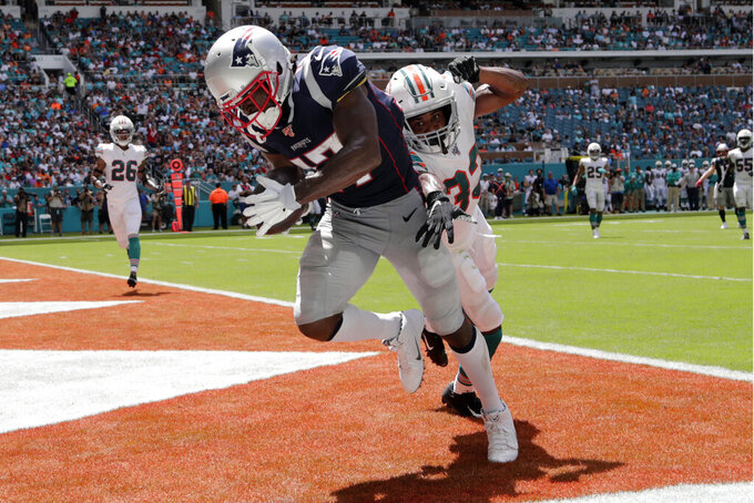 FILE - In this Sunday, Sept. 15, 2019, file photo, New England Patriots wide receiver Antonio Brown (17) scores a touchdown as Miami Dolphins cornerback Jomal Wiltz (33) defends during the first half at an NFL football game in Miami Gardens, Fla. Brown has indicated he's not retiring from the NFL, only a few days after announcing he was done with the league in a Twitter rant. Brown, who was released by the Patriots last week after playing only one game, says he'll practice at high schools one day a week, starting in Miami.  (AP Photo/Lynne Sladky, File)