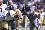 James Madison running back Cardon Johnson (25) tries to run around Elon defensive lineman Jordan Dollerson (91) during the first half of an NCAA football game in Harrisonburg, Va., Saturday, Oct. 6, 2018. (Daniel Lin/Daily News-Record via AP)