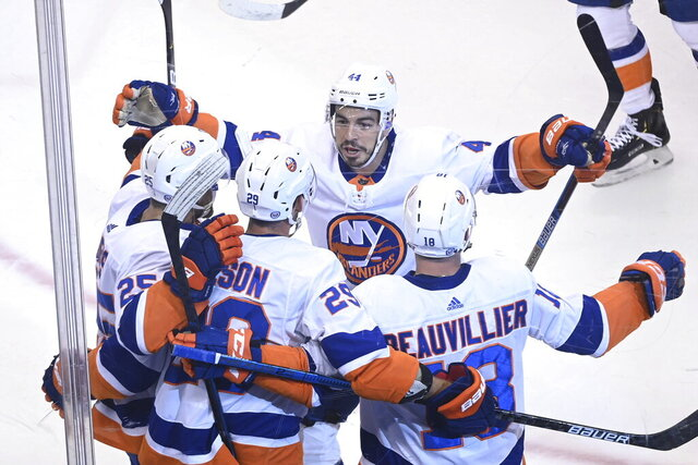 New York Islanders left wing Anthony Beauvillier (18) celebrates his goal against the Washington Capitals with teammates Devon Toews (25), Brock Nelson (29) and Jean-Gabriel Pageau (44) during the first period of an NHL Stanley Cup playoff hockey game in Toronto on Thursday, Aug. 20, 2020. (Nathan Denette/The Canadian Press via AP)