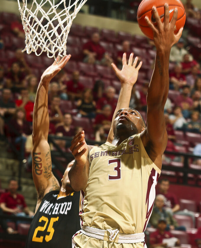Florida State guard Trent Forrest (3) makes a reverse layup as Winthrop forward Josh Ferguson (25) defends in the second half of an NCAA college basketball game in Tallahassee, Fla., Tuesday, Jan. 1, 2019. Florida State won 87-76. (AP Photo/Phil Sears)
