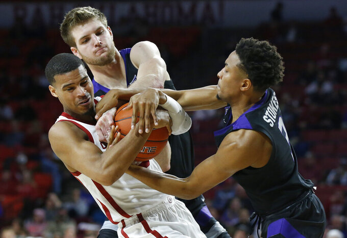 Oklahoma guard Miles Reynolds, left, and Kansas State forward Dean Wade, center, and guard Kamau Stokes fight for the ball in the second half of an NCAA college basketball game in Norman, Okla., Wednesday, Jan. 16, 2019. (AP Photo/Sue Ogrocki)