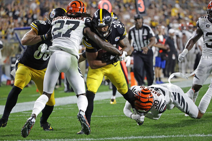 Pittsburgh Steelers running back James Conner (30) scores with Cincinnati Bengals free safety Jessie Bates (30) and cornerback Dre Kirkpatrick (27) defending during the first half of an NFL football game in Pittsburgh, Monday, Sept. 30, 2019. (AP Photo/Don Wright)