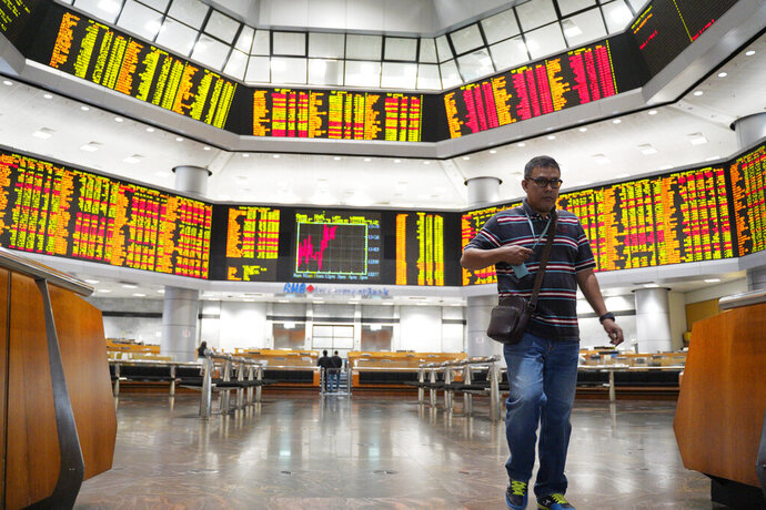 An investor walks in front of private stock trading boards at a private stock market gallery in Kuala Lumpur, Malaysia, Friday, Feb. 15, 2019. Asian shares are broadly lower, tracking a weak Wall Street session as traders await the conclusion of U.S.-China talks in Beijing. Japan's benchmark Nikkei 225 retreated 1.2 percent and the Kospi in South Korea gave up 1.6 percent on Friday. (AP Photo/Yam G-Jun)