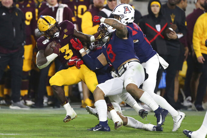 Arizona State's Eno Benjamin (3) is dragged down by a handful of Arizona defenders during the second half of an NCAA college football game Saturday, Nov. 30, 2019, in Tempe, Ariz. (AP Photo/Darryl Webb)