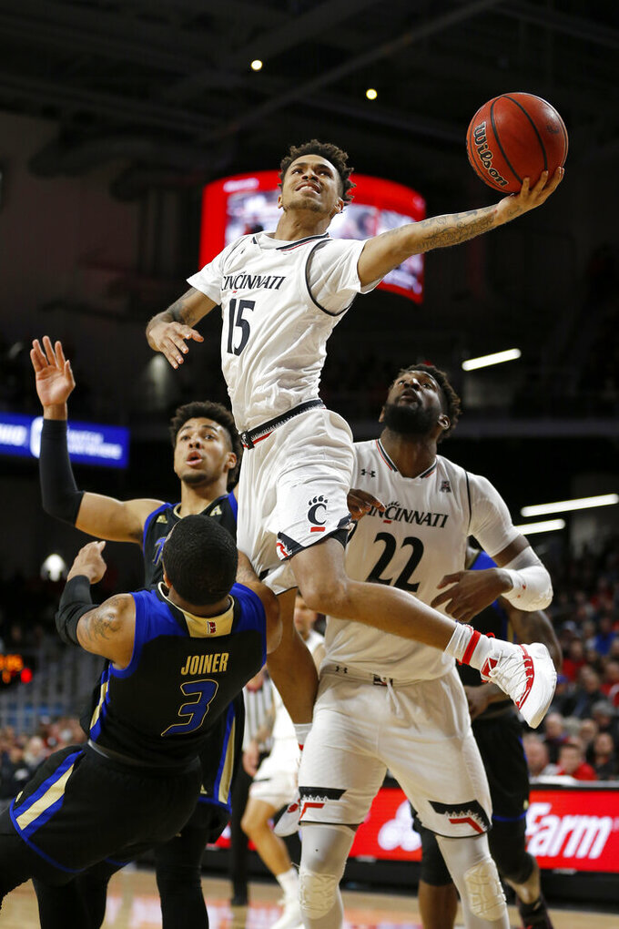 Cincinnati guard Cane Broome (15) leaps to the basket for a layup over Tulsa's Elijah Joiner (3) during the first half of an NCAA college basketball game Thursday, Jan. 24, 2019, in Cincinnati. (Sam Greene/The Cincinnati Enquirer via AP)