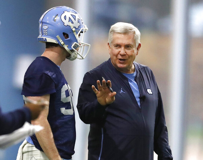 FILE - In this March 3, 2019, file photo, North Carolina head coach Mack Brown talks with Cooper Graham (96) during UNC's first spring football practice, in Chapel Hill, N.C. Brown is back for his second stint as coach of the Tar Heels and is pushing his players for more focus, execution and urgency in spring drills. (Ethan Hyman/The News & Observer via AP, File)/=