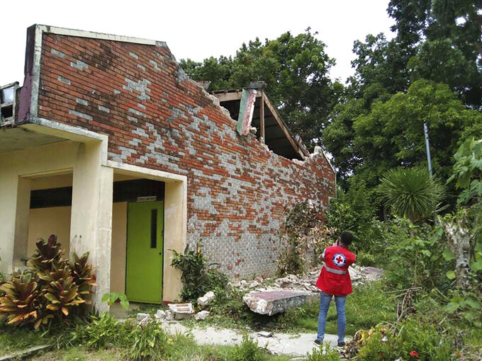 In this handout photo provided by the Philippine Red Cross, a volunteer takes photos of a damaged structure after a strong earthquake struck in Cataingan, Masbate province, central Philippines on Tuesday Aug. 18, 2020. A powerful and shallow earthquake struck a central Philippine region Tuesday, prompting people to dash out of homes and offices but there were no immediate reports of injuries or major damage. (Philippine National Red Cross via AP)