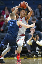 Stanford forward Oscar da Silva (13) looks to pass around San Diego guard Joey Calcaterra (2) during the first half of an NCAA college basketball game on Saturday, Dec. 21, 2019, in San Francisco. (AP Photo/D. Ross Cameron)
