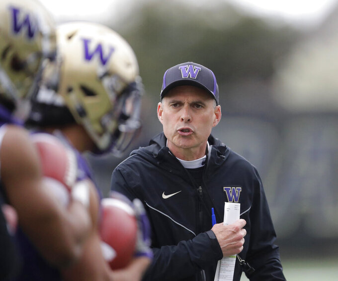 FILE - In this April 3, 2019, file photo, Washington coach Chris Petersen watches players as they run drills during NCAA college football practice in Seattle. The defending Pac-12 champion Huskies lost numerous starters to graduation, but Petersen's team hopes to contend for another league title in a conference race that looks wide open as the opening week approaches. (AP Photo/Ted S. Warren, File)