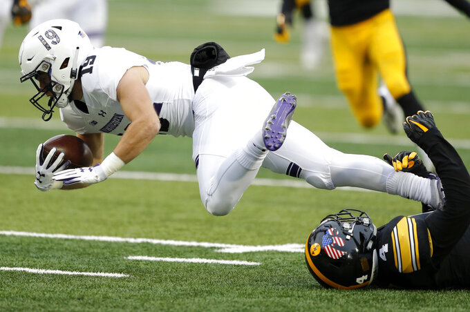 Northwestern wide receiver Riley Lees, left,  is tackled by Iowa's Josh Turner, right,  while returning a punt during the first half of an NCAA college football game, Saturday, Nov. 10, 2018, in Iowa City, Iowa. (AP Photo/Charlie Neibergall)