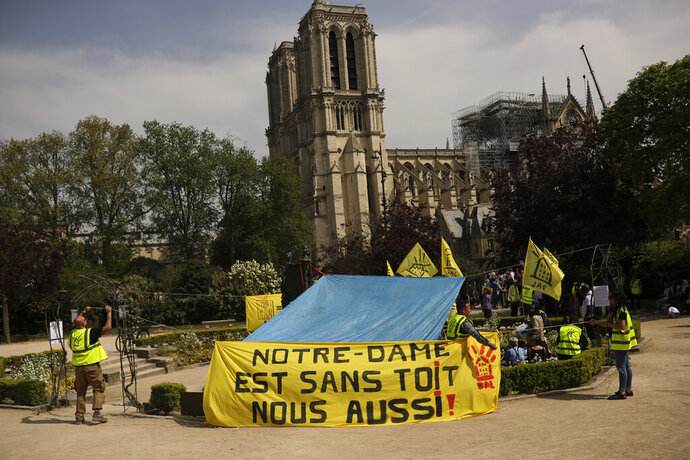 People fix a banner that reads in French: