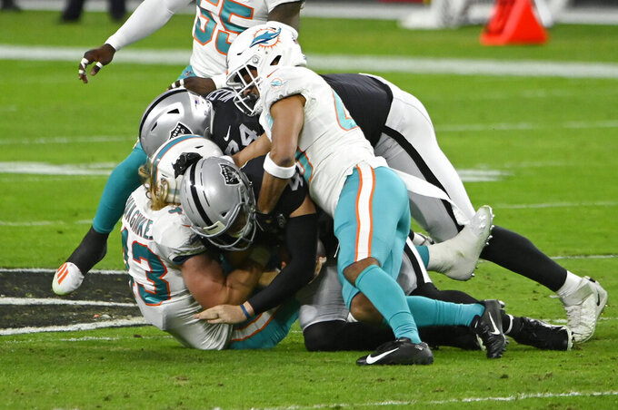 Miami Dolphins outside linebacker Andrew Van Ginkel, left, and defensive back Nik Needham, right, sack Las Vegas Raiders quarterback Derek Carr (4) during the first half of an NFL football game, Saturday, Dec. 26, 2020, in Las Vegas. (AP Photo/David Becker)