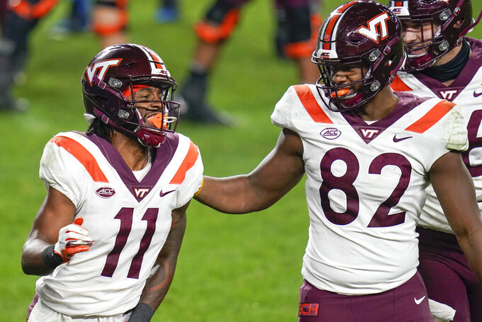 Virginia Tech wide receiver Tre Turner (11) celebrates with wide receiver Tayvion Robinson (83) after making a touchdown catch against Pittsburgh during the first half of an NCAA college football game, Saturday, Nov. 21, 2020, in Pittsburgh. (AP Photo/Keith Srakocic)