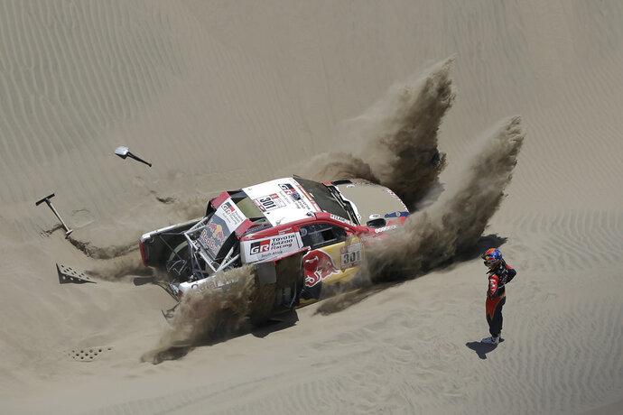 Co-driver Matthieu Baumel, of France, looks on as Driver Nasser Al-Attiyah, of Qatar, tries to unstuck their Toyota during the 4th stage of the 2018 Dakar Rally in San Juan de Marcona, Peru, Tuesday, Jan. 9, 2018. (AP Photo/Ricardo Mazalan)