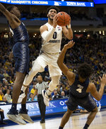 Marquette guard Markus Howard, center, drives to the basket against Georgetown forward Josh LeBlanc, left, and guard Jagan Mosely, right, during the first half of an NCAA college basketball game Saturday, March 9, 2019, in Milwaukee. (AP Photo/Darren Hauck)