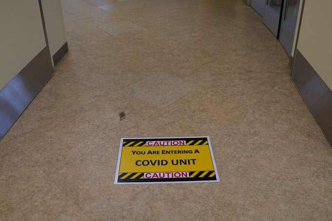 FILE - In this Jan. 7, 2021, file photo, a caution sign is placed on the floor of a COVID-19 unit at St. Joseph Hospital in Orange, Calif. U.S. hospital intensive care units in many parts of the country are straining under record numbers of COVID-19 patients.  (AP Photo/Jae C. Hong, File)