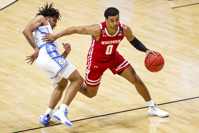 Wisconsin's D'Mitrik Trice (0) moves by North Carolina's RJ Davis during the second half of a first-round game in the NCAA men's college basketball tournament, Friday, March 19, 2021, at Mackey Arena in West Lafayette, Ind. (AP Photo/Robert Franklin)