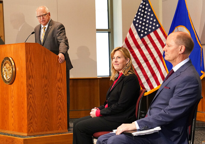 Minnesota Gov. Tim Walz speaks at a podium as Senate Majority Leader Paul Gazelka, R-East Gull Lake, right to left, and House Speaker Melissa Hortman, DFL-Brooklyn Park, listened in during a press conference Monday, May 17, 2021, in St. Paul, Minn., announcing the Legislature and Walz agreed to spend $52 billion on the next two-year budget. (David Joles/Star Tribune via AP)