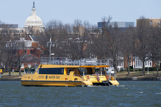 In this Friday March 19, 2021, photo a water taxi passes in the waterway next to Fort McNair, with the Capitol seen in the background in Washington. Iran has made threats against Fort McNair, a U.S. army base in Washington DC, and against the Army's vice chief of staff, according to two senior U.S. intelligence officials, who spoke on condition of anonymity to discuss national security matters. The threats are one reason the Army has been pushing for more security around the base, which sits alongside the bustling Waterfront district of Washington DC. (AP Photo/Jacquelyn Martin)