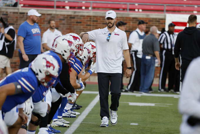 SMU offensive coordinator Garrett Riley greets some of the players before the team's NCAA college football game against Tulane in Dallas, Thursday, Oct. 21, 2021. (AP Photo/Michael Ainsworth)