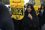 A demonstrator holds an anti-U.S. placard during an annual rally outside the former U.S. Embassy in Tehran, Iran, Monday, Nov. 4, 2019. Reviving decades-old cries of