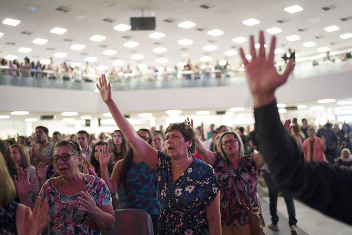 In this Sept. 2, 2018 photo, evangelicals raise their hands in prayer as they listen to a song during a service at the Assembly of God Victory in Christ Church in Rio de Janeiro, Brazil. In a Brazilian presidential election marked by uncertainties, there is little doubt about one thing: Evangelical voters will have a major impact. (AP Photo/Leo Correa)