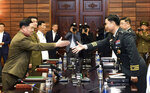 In this photo provided by South Korea Defense Ministry, South Korean Maj. Gen. Kim Do-gyun, right, tries to shakes hands with his North Korean counterpart Lt. Gen. An Ik San during a meeting at the northern side of Panmunjom in the Demilitarized Zone, North Korea, Thursday, June 14, 2018. The rival Koreas were holding rare high-level military talks Thursday to discuss reducing tensions across their heavily fortified border. (South Korea Defense Ministry via AP)