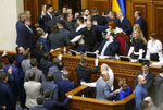 Ukrainian lawmakers scuffle around the rostrum during a parliament session in Kyiv, Ukraine, Thursday, Feb. 6, 2020. The Ukrainian parliament is considering changes to laws restricting the sale of farmland.(AP Photo/Efrem Lukatsky)
