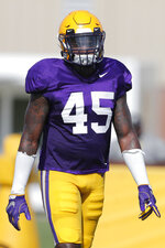 FILE - In this Wednesday, Aug. 7, 2019, file photo, LSU linebacker Michael Divinity Jr. (45) works out during an NCAA college football practice, in Baton Rouge, La. LSU coach Ed Orgeron says projected starting left tackle Saahdiq Charles and pass-rushing linebacker Michael Divinity Jr. are set to play when the sixth-ranked Tigers visit No. 9 Texas on Saturday. (AP Photo/Gerald Herbert, File)