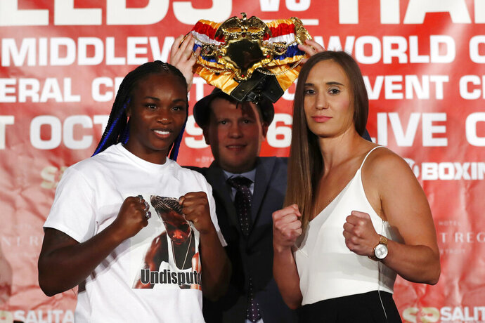 FILE - In this Aug. 14, 2019, file photo, Claressa Shields, left, stands with Ivana Habazin and promotor Dmitriy Salita during a press conference in Detroit. Claressa Shields tries for a third time to win a world title in three divisions. The first bout against Ivana Habazin was scratched because Shields injured her knee in training. The second attempt, well, even for the wacky world of boxing weigh-ins, this one went off the rails. Habazin's trainer was struck by Shields' brother and hospitalized: Artis Mack was charged with assault and the fight again was postponed. Shields and Habazin have kept the week leading up to Saturday's 154-pound fight in Atlantic City, New Jersey free of drama or any other distractions that could cancel the bout. (AP Photo/Carlos Osorio, File)
